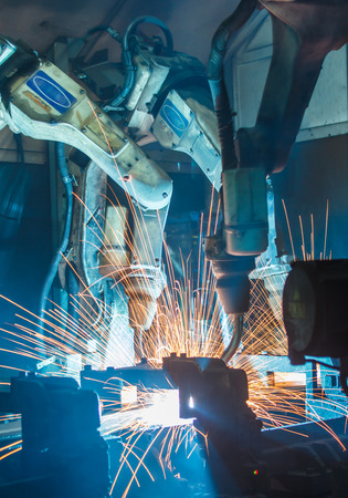 automotive: Team welding robots represent the movement. In the automotive parts industry. Stock Photo