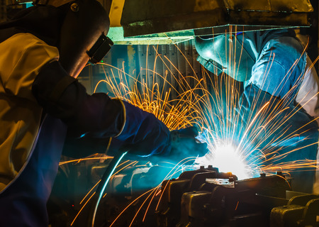 skilled labour: worker with protective mask welding metal