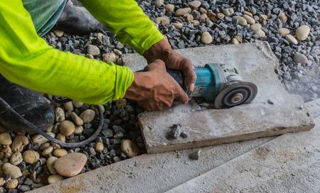 Construction workers cut bricks