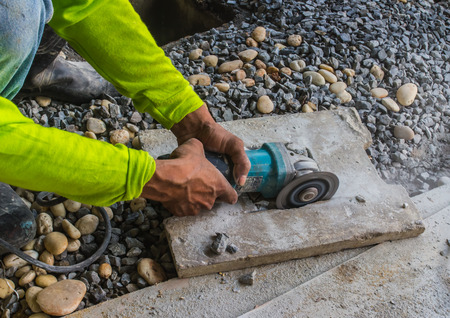 tile cutter: grinder worker cuts a stone the electric tool
