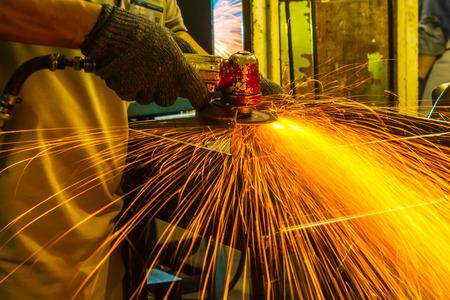 The worker grinding metal in manufacturing plant