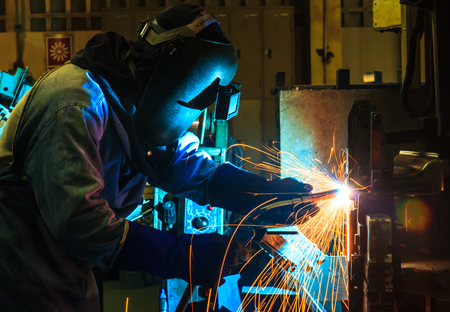 prefabricate: Welder man welding, spark, light and hot. Metal, iron work, and work. Mask and gloves for protection. Industry, industrial. Stock Photo