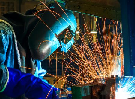 welding mask: skilled working factory welder