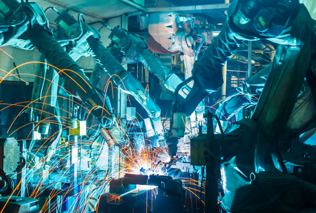 production line factory: Welding robots movement in a car factory