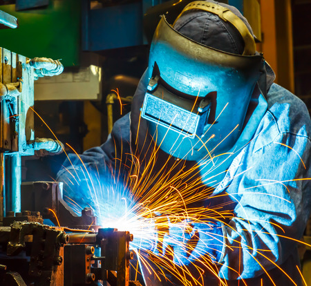 improvisation: welding worker in the automotive part in Industrial Stock Photo