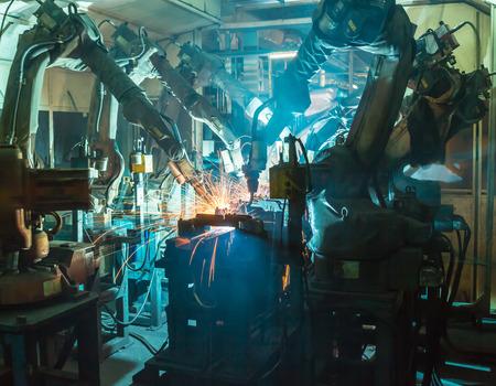 asamblea: Robots de soldadura movimiento en una fábrica de coches