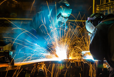 protective mask: worker welder with protective mask welding metal
