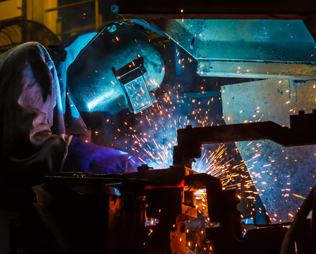skilled labour: welding worker in the automotive part in Industrial Stock Photo