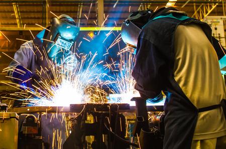 welding worker: welding worker in the automotive part in Industrial Stock Photo