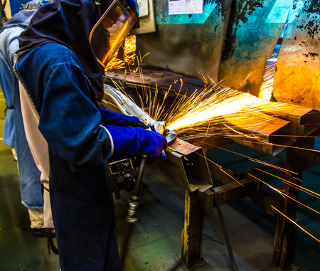 prefabricate: The worker grinding metal in manufacturing plant