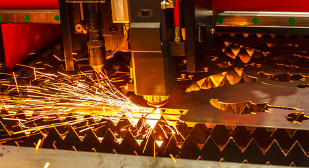 Laser cutting machine cutting the sheet metal with the sparking light. modern industrial technology Stockfoto