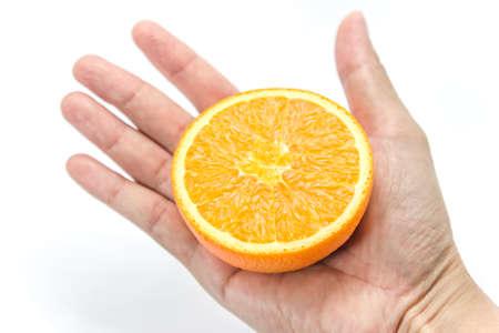 Hand hold half cut orange fruit on white background