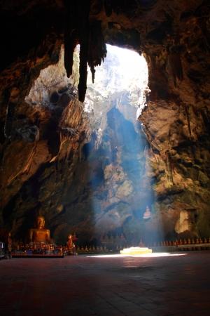 dark cave: The sun beam in the  cave with Buddha, Phetchaburi Thailand Stock Photo