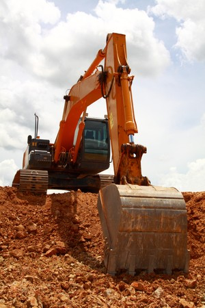 flatten: Excavator under cloudy sky Stock Photo