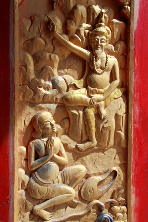 native Thai style wood carving on door of Buddhist church. photo