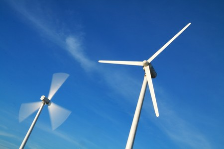 two wind turbines in Motion and standstill blade with blue sky.