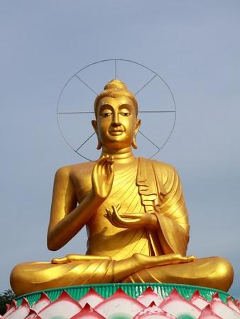 big gold buddha in chinese style with clear sky,Rachaburi Thailand. photo