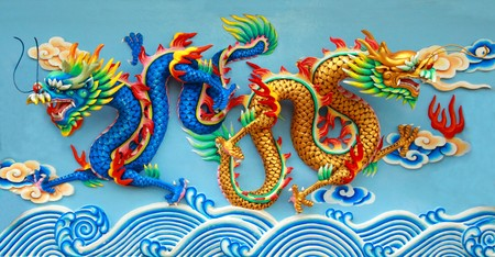 blue and gold chinese dragon statue at the wall of chinese temple in Thailand.