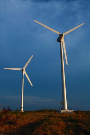 Modern wind turbines or wind mills in cloudy sky photo