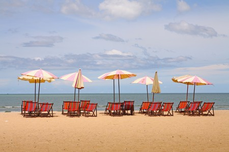 lounger: group of beach chairs with umbrella and yacht at ocean front  Stock Photo