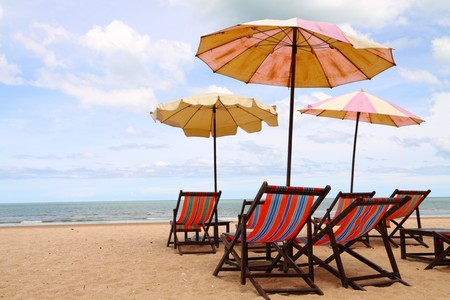 Exotic scenic with sunshade parasols and chairs by a beach in Thailand, horizontal image