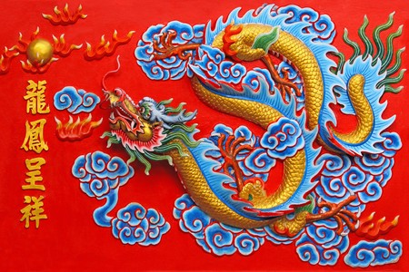 A chinese golden dragon at red wall in chinese temple , Pattaya Thailand.