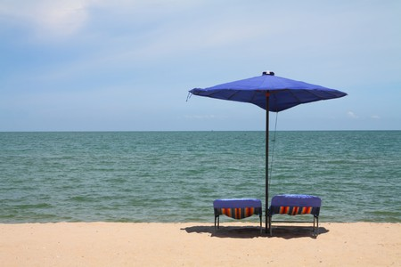 Deckchairs and parasol on the white sand beach facing the beach, Thailand photo