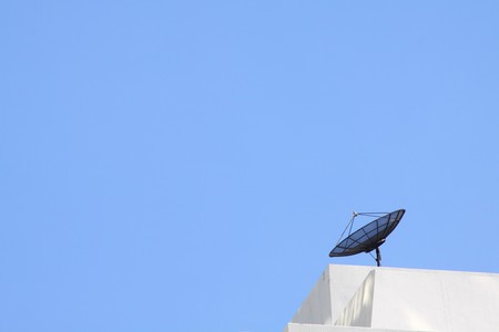 small satelite dish on building with blue sky. photo