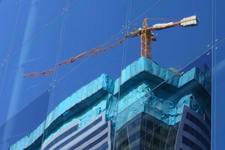 reflection of  glass building and crane with blue sky background  photo