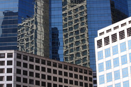 high rise buildings: new office building in business center with reflection in glass wall