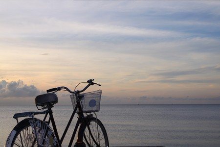 old bicycle with twilight sky and the sea in Thailand. Stock Photo