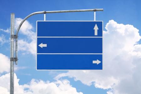 cruce de caminos: Signo de la carretera en blanco, tres flecha azul con cielo nublado listo para su texto personalizado.