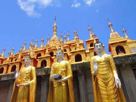 three of Myanmar style buddha statue with gold pagoda background, Phrae province , north of Thailand. photo