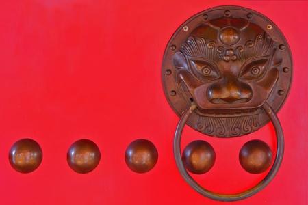Chinese lion head door knocker on red door photo