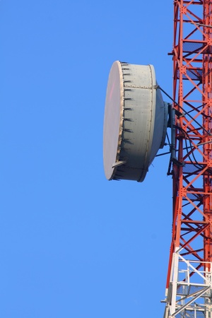 Part of a telecommunication tower with antennas against blue sky photo