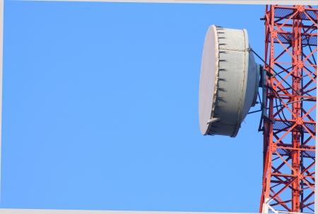 Part of a telecommunication tower with antenna against blue sky photo