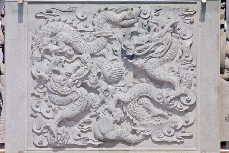 asia dragon stone carved pattern on a wall photo