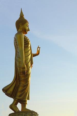 Walking golden Buddha statue in  morning sky Stock Photo - 8861366