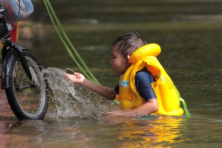 BANGKOK THAILAND - OCTOBER 29 : An Thai boy plays in flood water on the street on October 29, 2011 at Tha Phra Jun. Bangkok, Thailand.