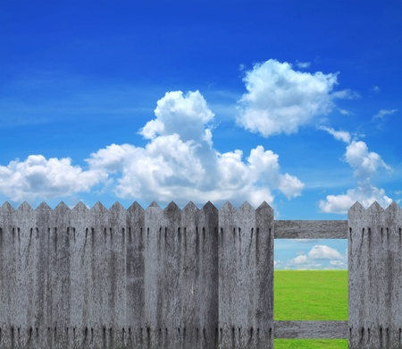 old wooden fence with green field and sky background. Stock Photo - 11222356