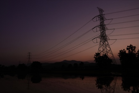 High voltage Electric power lines on twilight sky background photo