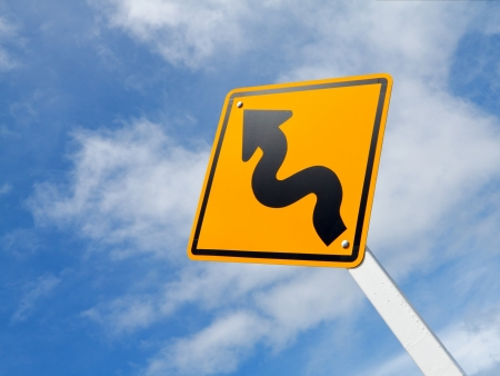 Curved Road Traffic Sign over blue sky photo