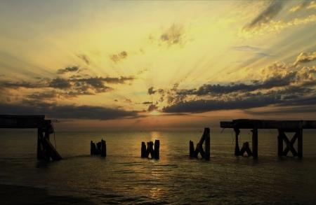 ingestorte brug in de zee met zonsopgang Aangetaste lagers en stortte in betonnen vloer Stockfoto