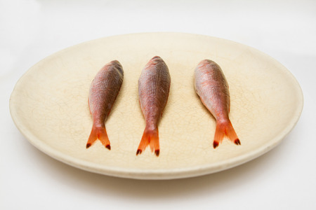 ful: three small fish on dish on white background