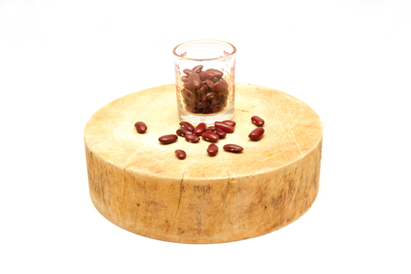 rajma: isolated kidney red bean in glass measuring cup on asian wooden cutting board on white background