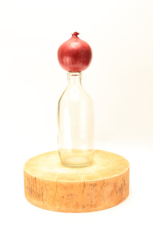 aftertaste: isolated red onion on clear bottle on asian traditional cutting board