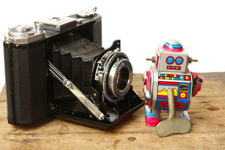 tin robot: Tin robot toy with Antique Vintage Retro Old Photo Camera compose on wooden plank on white background