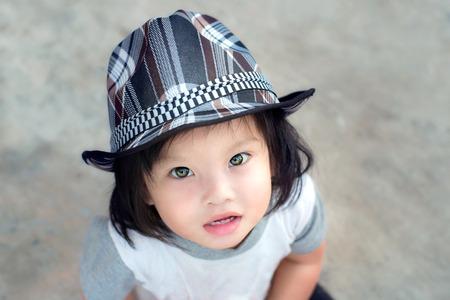 girl squatting: Children wear hat look at camera. Stock Photo