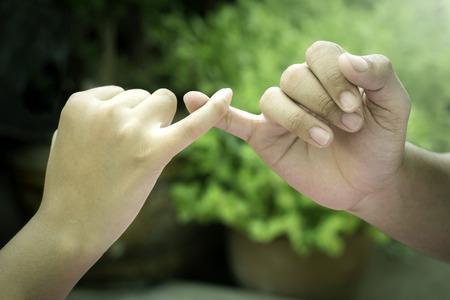 promising: Hand in hand make promise.