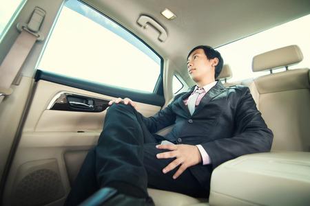 passengers: Businessman sitting in luxury car.